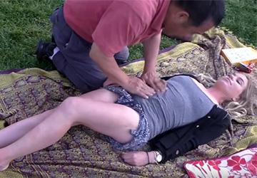 【素人マッサージ】芝生の上でマッサージを受ける金髪白人女性、ノーブラで思いっきり乳首が浮いていた