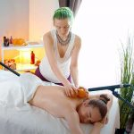 【マッサージ動画】ノーブラのセラピストがオレンジを使って背中をマッサージする様子