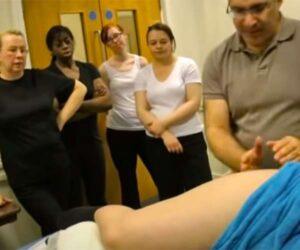 【マッサージ講習会動画】真剣な表情で下半身マッサージをされる女性を見つめる受講者達